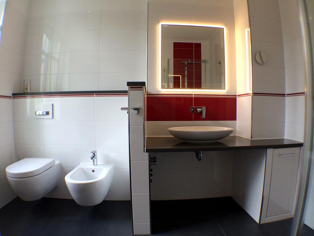 Aufsatzwaschtisch mit Wandarmatur und in die Wand eingelassenem Spiegelschrank
